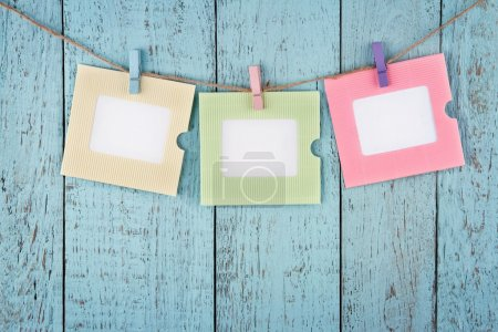 Three empty photo frames hanging with clothespins