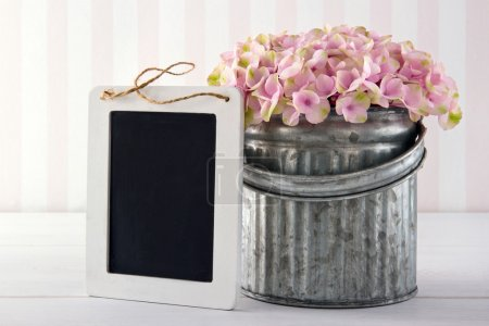 Photo for Pink hydrangea flowers in a metal vase on vintage background with empty blackboard for copy space - Royalty Free Image