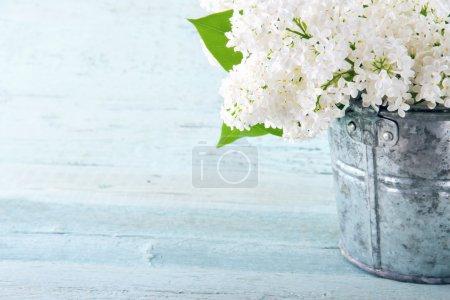 Photo pour Bouquet de fleurs blanches printemps lilas dans un vase en bois bleu sur fond clair de chic minable - image libre de droit