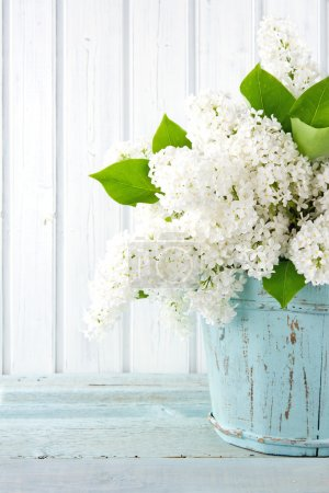 Photo for Bouquet of white lilac spring flowers in a wooden blue vase on light shabby chic background - Royalty Free Image