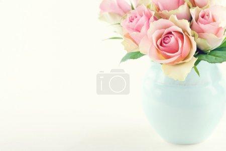 Pink roses in a light blue vase