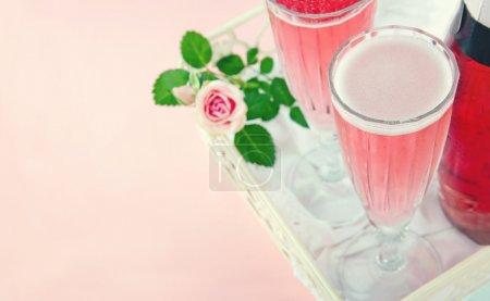Photo pour Deux verres de champagne rose avec une rose sur un fond couleur pastel vintage - image libre de droit