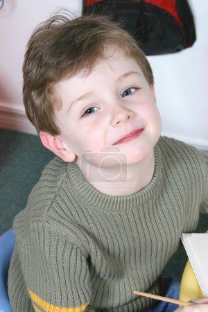 Foto de Niño guapo y feliz sentado en una mesa de edad preescolar. rodado con la canon 20D. - Imagen libre de derechos