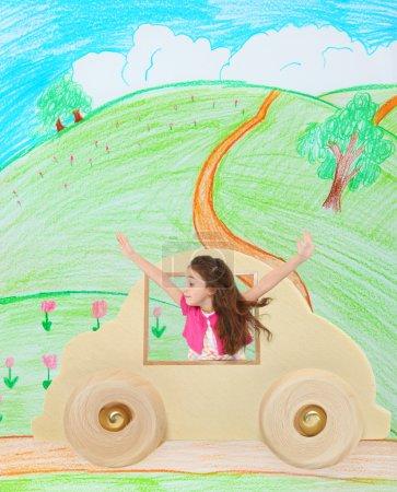 Photo pour Année 6 adorable vieux français jeune américaine dans une voiture de jouet en bois traversant une route de campagne imaginaire. - image libre de droit