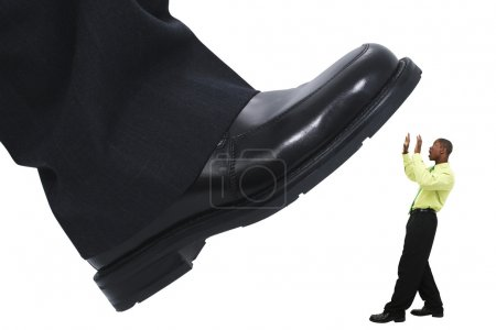 Photo for Large foot ready to step down on young business man. Shot in studio over white with the Canon 20D. - Royalty Free Image