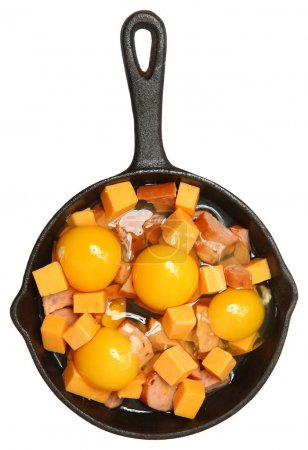 Photo pour Œufs crus, fromage et saucisse dans une poêle en fonte isolée au-dessus du blanc . - image libre de droit