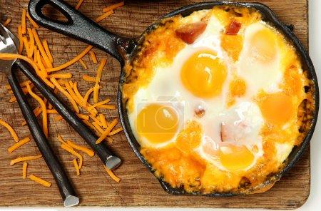 Photo pour Poêle cuit oeufs et saucisse au fromage sur la table - image libre de droit