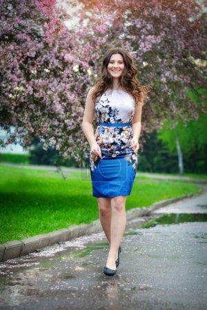 Photo pour Belle fille marche dans le jardin fleuri, printemps - image libre de droit