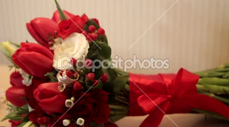 Bridal bouquet of red roses and rings on the table