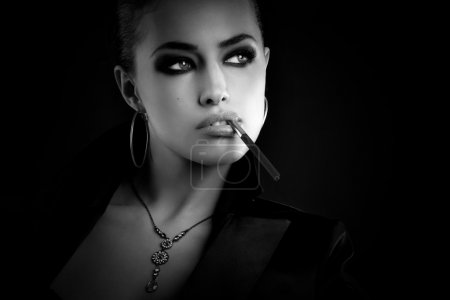 Photo for Black and white fashion portait of a beautiful young woman with cigarette - Royalty Free Image