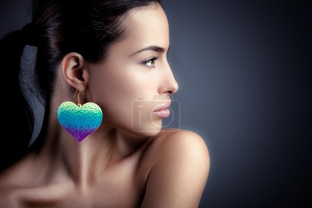 Photo for Beautiful young woman wearing colorful earrings, profile portrait, studio - Royalty Free Image
