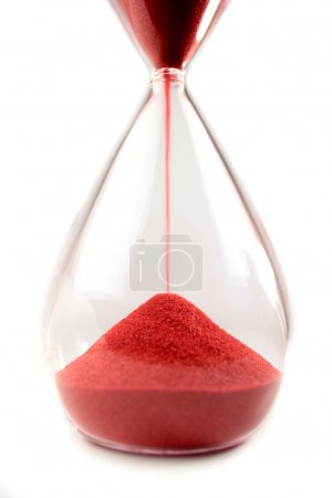 Hourglass with red sand on white background