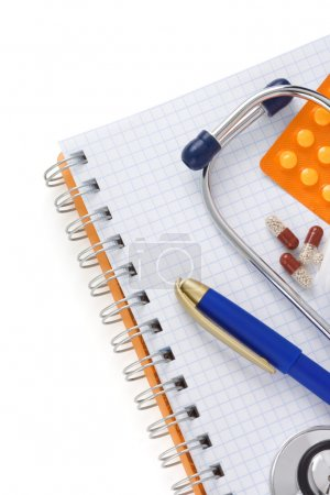 stethoscope with pills and notebook