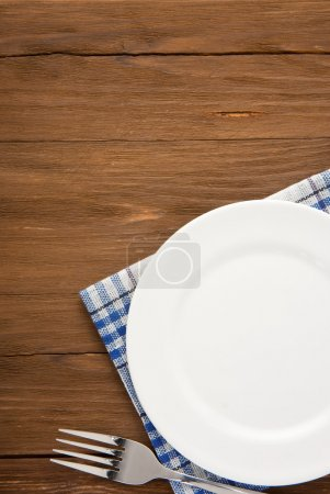 Photo for White plate and fork at napkin on wooden background - Royalty Free Image