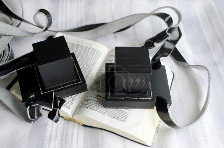 Foto de Un conjunto de tefillin incluye el brazo-tefillin (izquierda) y la cabeza-tefillin en un libro de rogación y talit. - Imagen libre de derechos