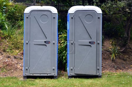 Photo for Two portable bathrooms in the field of a camp ground. - Royalty Free Image