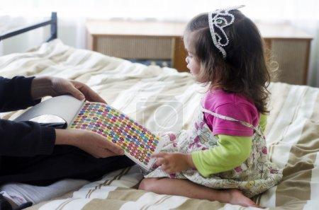 Photo pour Petite fille a été récompensée pour bonne conduite par sa mère avec des autocollants colorés . - image libre de droit