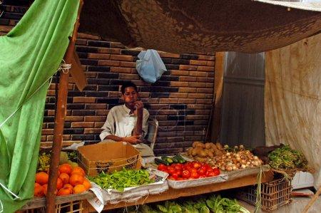 Photo pour Assouan - 28 avril : un jeune homme égyptien vendant des légumes au marché d'aswan, Egypte avril production totale des cultures agricoles de le 28 2007.egypt a augmenté de plus de 20 pour cent dans la dernière décennie. - image libre de droit