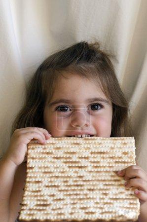 Jewish girl eating a matzo in passover Jewsih holi...