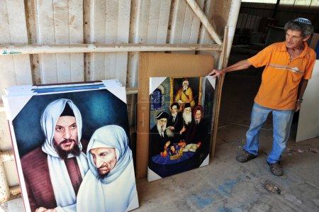 """Photo pour NETIVOT, ISR - 24 AOÛT : L'homme juif tient des peintures à l'huile de """"Baba Sali"""" sur Août 24 2009.Rabbi Yisraël Abuhatzeira était kabbaliste qui célèbre pour sa prétendue capacité à faire des miracles à travers ses prières . - image libre de droit"""
