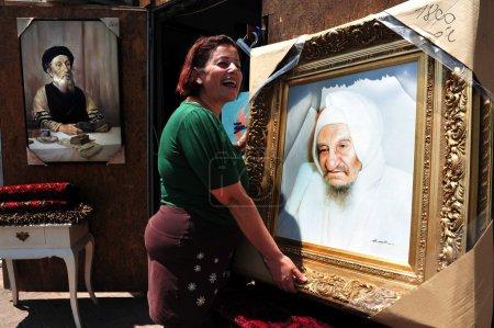 """Photo pour NETIVOT, ISR - 24 AOÛT : Femme juive tient des peintures à l'huile de """"Baba Sali"""" sur Août 24 2009.Rabbi Yisraël Abuhatzeira était kabbaliste qui célèbre pour sa prétendue capacité à faire des miracles à travers ses prières . - image libre de droit"""