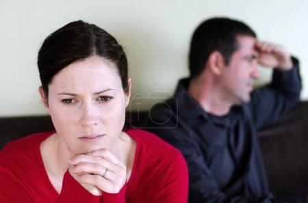Photo pour Portrait de jeunes couples malheureux qui sont tombés sur un désaccord assis sur un canapé. Femme à l'avant et l'homme à l'arrière-plan . - image libre de droit