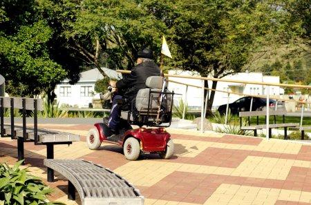 Photo pour KAITAIA, NZ - 15 AOÛT : scooter de mobilité de conduite d'homme âgé le 15 août 2013.Actuellement, l'assurance-maladie des États-Unis n'approuvera pas un fauteuil roulant électrique pour les personnes qui n'ont pas besoin d'utiliser la chaise à l'intérieur de leur propre maison . - image libre de droit