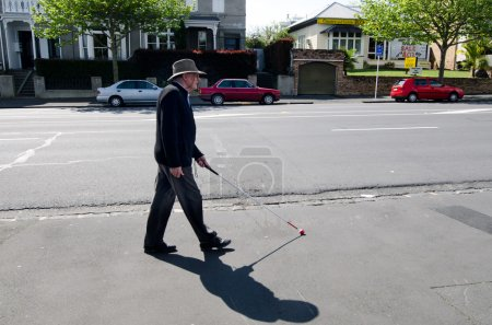 Blind man walks with a cane in the street