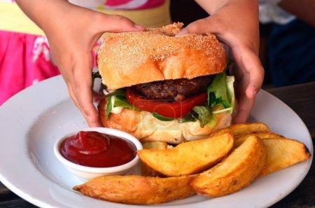 Foto de Manos de una niña lista para comerse una hamburguesa grande. Foto de concepto - Imagen libre de derechos