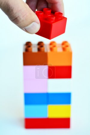Photo for Mans hand puts a red toy block on top of a building blocks tower in the background. concept photo of imagination, creativity, planning and ideas - Royalty Free Image
