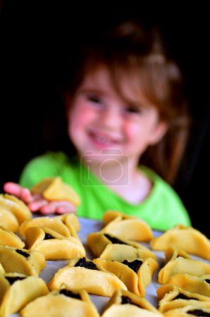 Photo for Jewish child eats Hamentashen, Ozen Haman, cookies on Purim Jewish holiday. - Royalty Free Image