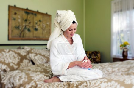 Young woman applies moisturiser to her skin