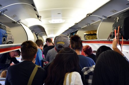 Photo for MELBOURNE - APR 10 2014:Interior of airplane with passengers get on board.According to Us Travel Association, the average age of leisure travelers is 47.5 years old. - Royalty Free Image