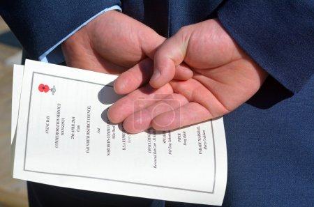 Photo pour Mains de Nouvelle-Zélande armée agent détient anzac ordre de service au cours d'une journée anzac Mémorial de guerre national en Nouvelle Zélande. - image libre de droit