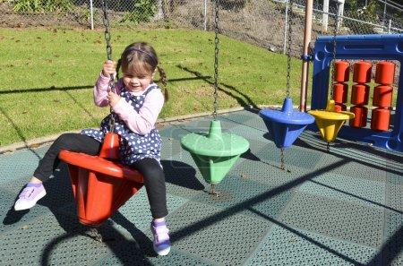 Photo pour Petite fille jouer dans une aire de jeux pour enfants moderne dans le parc . - image libre de droit