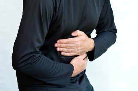 Photo pour Homme avec des douleurs abdominales debout sur fond blanc. Torse et mains. Concept photo des soins de santé et médical - image libre de droit