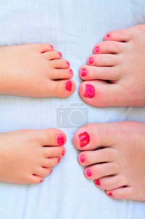 Mother and child paint their feet with nail polish