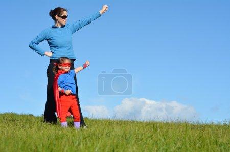 Foto de Superhéroe madre e hija contra el dramático fondo azul del cielo con espacio de copia . - Imagen libre de derechos