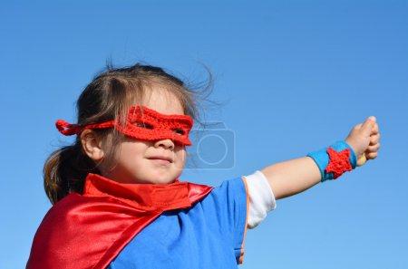 Foto de El niño superhéroe corre en un campo verde contra el dramático fondo azul del cielo con espacio para copiar. concepto foto de Super héroe, poder de la muchacha, jugar fingir, infancia, imaginación . - Imagen libre de derechos