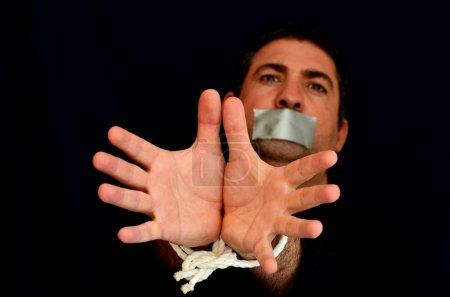 Photo pour Enlevé, maltraité, otage, victime homme avec les mains liées par la corde dans le stress émotionnel et la douleur, peur, restreint, piégé, appel à l'aide, lutte, terrifié, enfermé dans une cellule de la cage . - image libre de droit