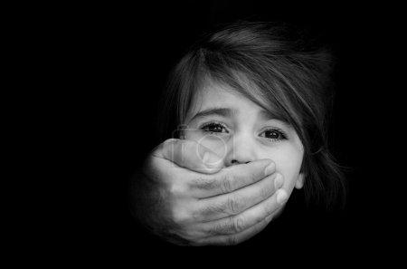 Photo pour De fortes mains masculines couvrent le visage de la petite fille de stress émotionnel, de douleur, de peur, d'appel à l'aide, de lutte, d'expression terrifiée.Concept Photo d'enlèvement, disparu, kidnappé, victime, otage, enfant maltraité - image libre de droit