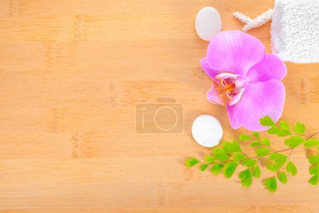 spa concept, lilac orchid and white towels on the bamboo backgro
