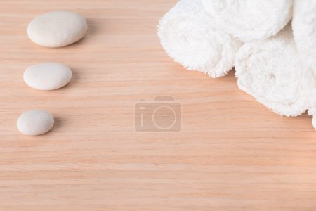 Spa still life with stone and white towel on wood background