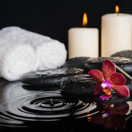 Photo pour Concept spa de pierres zen avec gouttes violette orchidée (phalaenopsis), bougies, serviettes de bain blancs avec reflet d'ondulation sur l'eau - image libre de droit