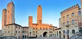 Panoramic view of famous Piazza del Duomo in San Gimignano at sunset, Tuscany, Italy
