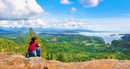 Photo for Woman sitting on a rock and enjoying the beautiful view on Vancouver Island, British Columbia, Canada. - Royalty Free Image