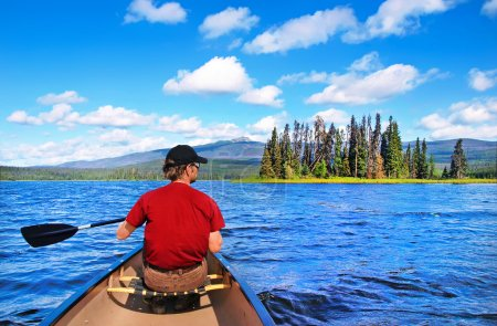 Man canoeing on a lake in the wilderness of British Columbia, Canada