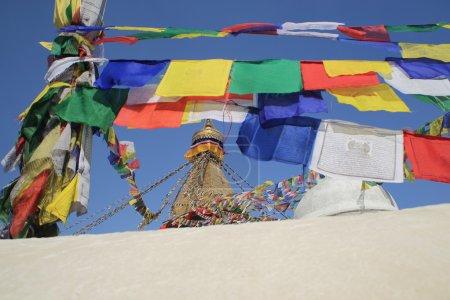 Foto de El stupa grande blanco de la oración de budistas color boudhanath-bodhnath-muchos banderas cuelgan de sus ojos la Torre Dorada 13 plantas de Buda mirando a los 4 puntos cardinales. Katmandú-nepal. - Imagen libre de derechos
