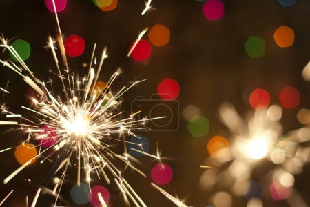 Photo for Sparkler and colorful bokeh christmas new year background - Royalty Free Image