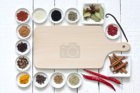 Photo for Spices and dried vegetables with cutting board on white planks - Royalty Free Image